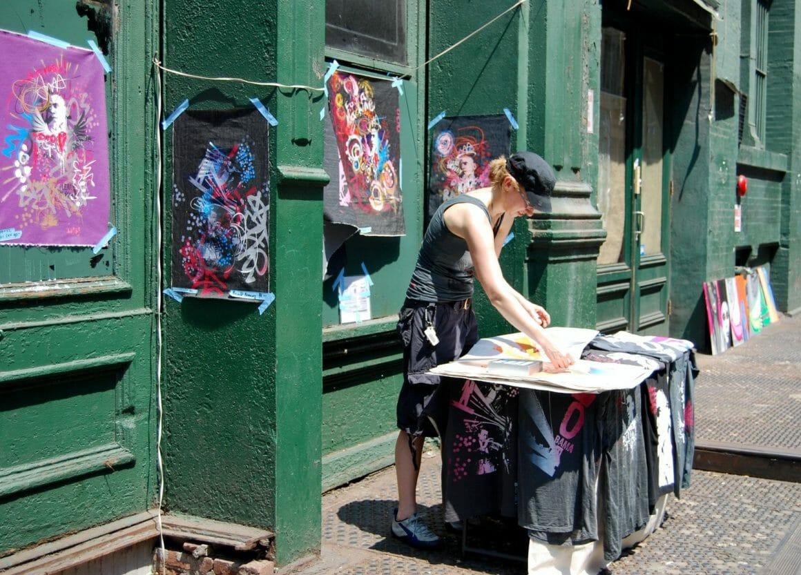 woman in black tank top standing beside green wooden door